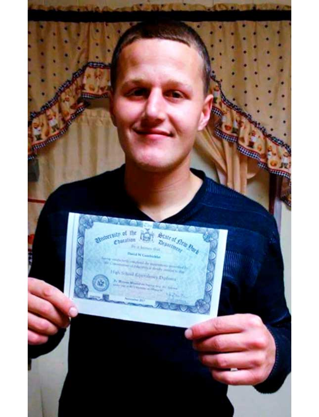 David Gambicher, a reentry program success story, holding up his High School equivalency certificate
